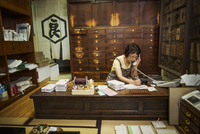 A traditional wagashi sweet shop. A woman working at a desk using a laptop and phone.   11093012363| 写真素材・ストックフォト・画像・イラスト素材|アマナイメージズ