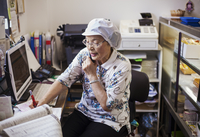 A mature woman at a desk in the office of a noodle production factory on the telephone.   11093012600| 写真素材・ストックフォト・画像・イラスト素材|アマナイメージズ