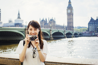 Young Japanese woman enjoying a day out in London, standing on the Queen's Walk by the River Thames. 11093013806| 写真素材・ストックフォト・画像・イラスト素材|アマナイメージズ
