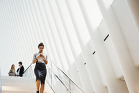 A woman walking down a staircase in the Oculus building, the World Trade Centre hub, modern architectural design with a ribbed v 11093014881| 写真素材・ストックフォト・画像・イラスト素材|アマナイメージズ