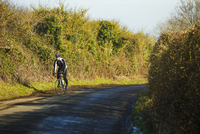 A cyclist riding along a country road on a clear sunny winter day. 11093015012| 写真素材・ストックフォト・画像・イラスト素材|アマナイメージズ
