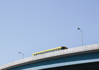 A yellow schoolbus driving over an elevated roadway against a blue sky. 11093015081| 写真素材・ストックフォト・画像・イラスト素材|アマナイメージズ