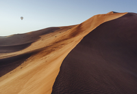 A sand dune in the desert, with a hot air balloon in the blue sky beyond. 11093015131| 写真素材・ストックフォト・画像・イラスト素材|アマナイメージズ