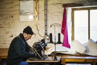 Man in a sailmaker's workshop sewing a sail with a sewing machine. 11093015243| 写真素材・ストックフォト・画像・イラスト素材|アマナイメージズ