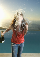 Woman standing in front of a swimming pool, holding bottle of champagne, spitting at camera. 11093015274| 写真素材・ストックフォト・画像・イラスト素材|アマナイメージズ