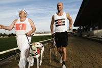 Two men in sportswear running on a racetrack with two greyhounds on leads. 11093015301| 写真素材・ストックフォト・画像・イラスト素材|アマナイメージズ