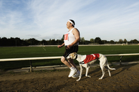 Man in sportswear running on a racetrack, with a white greyhound wearing red bib with number one. 11093015302| 写真素材・ストックフォト・画像・イラスト素材|アマナイメージズ