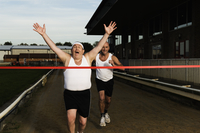Two men in sportswear running towards the finish line of a race track. 11093015305| 写真素材・ストックフォト・画像・イラスト素材|アマナイメージズ