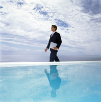 A man in a suit walking along a swimming pool, carrying a laptop. 11093015426| 写真素材・ストックフォト・画像・イラスト素材|アマナイメージズ