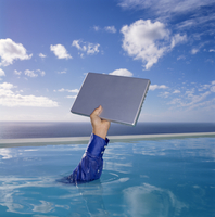 Human arm in blue shirt sleeve in swimming pool, holding aloft a laptop computer, sky and clouds. 11093015429| 写真素材・ストックフォト・画像・イラスト素材|アマナイメージズ