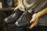Close up of man standing in a shoemaker's workshop, holding a pair of handmade leather lace up cycling shoes. 11093015589| 写真素材・ストックフォト・画像・イラスト素材|アマナイメージズ