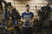 Man standing in a shoemaker's workshop, holding a pair of brown leather laced cycling shoes. 11093015591| 写真素材・ストックフォト・画像・イラスト素材|アマナイメージズ