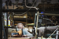 A senior grey haired woman worker sitting at a leather stitching machine in a shoemaker's workshop. 11093015599| 写真素材・ストックフォト・画像・イラスト素材|アマナイメージズ