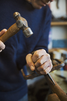 Man standing in a workshop, holding a hammer and wood chisel, working on a piece of wood. 11093015790| 写真素材・ストックフォト・画像・イラスト素材|アマナイメージズ