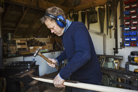 Man standing in a workshop, wearing ear protectors, holding a hammer, working on a piece of wood. 11093015794| 写真素材・ストックフォト・画像・イラスト素材|アマナイメージズ