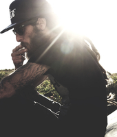 Side view of bearded man wearing baseball cap and sunglasses, smoking cigarette, tattooed arms, sunlight. 11093016263| 写真素材・ストックフォト・画像・イラスト素材|アマナイメージズ