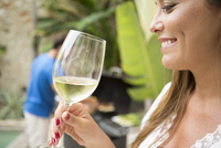 A woman holding a glass of wine and smiling. 11093016445| 写真素材・ストックフォト・画像・イラスト素材|アマナイメージズ