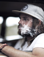 Bearded young man wearing baseball cap sitting in a car, smoking cigarette, cigarette smoke. 11093016524| 写真素材・ストックフォト・画像・イラスト素材|アマナイメージズ