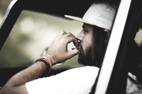 Bearded young man wearing baseball cap sitting in a car, smoking cigarette. 11093016526| 写真素材・ストックフォト・画像・イラスト素材|アマナイメージズ