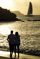 Rear view of couple standing on a sandy beach by the ocean, cliffs and a sailing boat in the distance at sunset. 11093016697| 写真素材・ストックフォト・画像・イラスト素材|アマナイメージズ