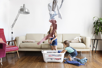 Young boy and girl standing in front of sofa, throwing laundry in air, laundry basket on hardwood floor. 11093016936| 写真素材・ストックフォト・画像・イラスト素材|アマナイメージズ