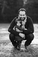 Bearded man crouching on lawn, hugging young girl wearing checkered dress, smiling at camera. 11093016975| 写真素材・ストックフォト・画像・イラスト素材|アマナイメージズ