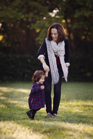 Smiling woman holding hand of young girl wearing checkered dress, standing outdoors on lawn. 11093016982| 写真素材・ストックフォト・画像・イラスト素材|アマナイメージズ