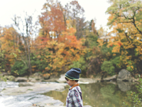 Young boy wearing checkered shirt and knit hat standing outdoors by a river, trees with autumn foliage. 11093017553| 写真素材・ストックフォト・画像・イラスト素材|アマナイメージズ
