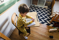 High angle view of young boy with brown hair wearing yellow pajamas sitting at a table in a nursery, writing into notebook. 11093017596| 写真素材・ストックフォト・画像・イラスト素材|アマナイメージズ