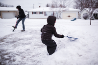 Young boy and man shoveling snow in a driveway. 11093017604| 写真素材・ストックフォト・画像・イラスト素材|アマナイメージズ