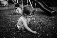 High angle view of bare chested young girl kneeling on a lawn, picking clover, boy in background. 11093017747| 写真素材・ストックフォト・画像・イラスト素材|アマナイメージズ
