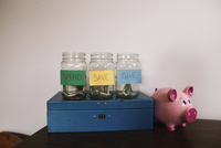 Close up of blue metal box, three glass jars with money and handwritten labels and a pink piggy bank. 11093017923| 写真素材・ストックフォト・画像・イラスト素材|アマナイメージズ