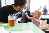 A man and a toddler, a father and daughter seated at a table, and a glass of beer on the table. 11093018144| 写真素材・ストックフォト・画像・イラスト素材|アマナイメージズ