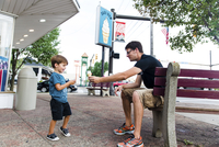 A man sitting on a bench in front of an ice cream parlour, holding out an ice cream cone to a boy, father and child. 11093018174| 写真素材・ストックフォト・画像・イラスト素材|アマナイメージズ