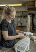 Blond woman standing in a workshop, cutting bubble wrap with pair of scissors, wrapping a parcel for delivery or posting. 11093018871| 写真素材・ストックフォト・画像・イラスト素材|アマナイメージズ