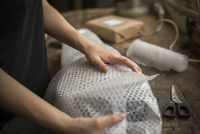 A woman wrapping an item in bubble wrap, a parcel being prepared for despatch. 11093018872| 写真素材・ストックフォト・画像・イラスト素材|アマナイメージズ