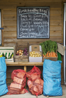 Handwritten blackboard on wall and crates with fresh vegetables and stack of firewood in red net bags outside a farm shop. 11093019006| 写真素材・ストックフォト・画像・イラスト素材|アマナイメージズ