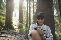 Woman writing in journal against tree in woods 11096003642| 写真素材・ストックフォト・画像・イラスト素材|アマナイメージズ