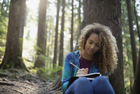 Woman writing in journal against tree in woods 11096003643| 写真素材・ストックフォト・画像・イラスト素材|アマナイメージズ