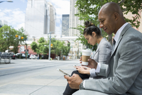 Business people coffee texting cell phone urban bench 11096012539| 写真素材・ストックフォト・画像・イラスト素材|アマナイメージズ