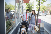Family with shopping bags on sidewalk at storefront 11096012657| 写真素材・ストックフォト・画像・イラスト素材|アマナイメージズ