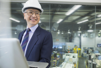 Smiling manager using laptop in factory 11096016190| 写真素材・ストックフォト・画像・イラスト素材|アマナイメージズ