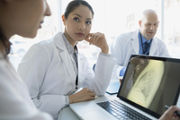 Doctors viewing x-ray on laptop in meeting 11096016438| 写真素材・ストックフォト・画像・イラスト素材|アマナイメージズ