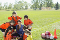 girls soccer team looking at playbook with coach 11096022448| 写真素材・ストックフォト・画像・イラスト素材|アマナイメージズ