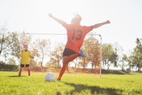 Young female soccer player about to kick soccer ball. 11096025141| 写真素材・ストックフォト・画像・イラスト素材|アマナイメージズ