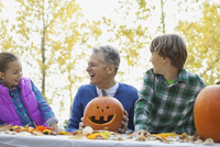 Happy grandfather and boy with jack o lanterns looking at girl in park 11096041281| 写真素材・ストックフォト・画像・イラスト素材|アマナイメージズ