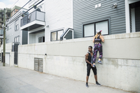 Suspicious young man lifting young woman over urban wall 11096042543| 写真素材・ストックフォト・画像・イラスト素材|アマナイメージズ