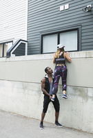 Young man lifting young woman over urban wall 11096042544| 写真素材・ストックフォト・画像・イラスト素材|アマナイメージズ