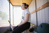 Pensive middle school girl softball player listening to music with headphones in dugout 11096043500| 写真素材・ストックフォト・画像・イラスト素材|アマナイメージズ