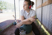 Serious middle school girl softball player listening to music with headphones in dugout 11096043501| 写真素材・ストックフォト・画像・イラスト素材|アマナイメージズ